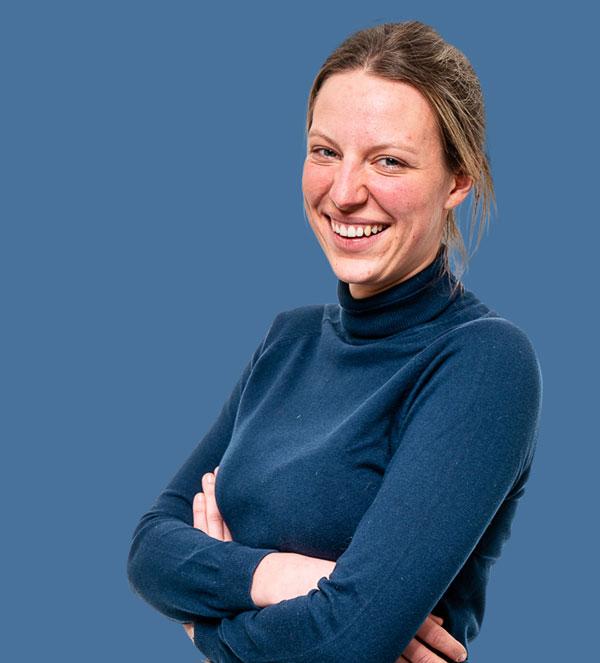 Vrouw blauwe coltrui gekruiste armen lacht naar camera
