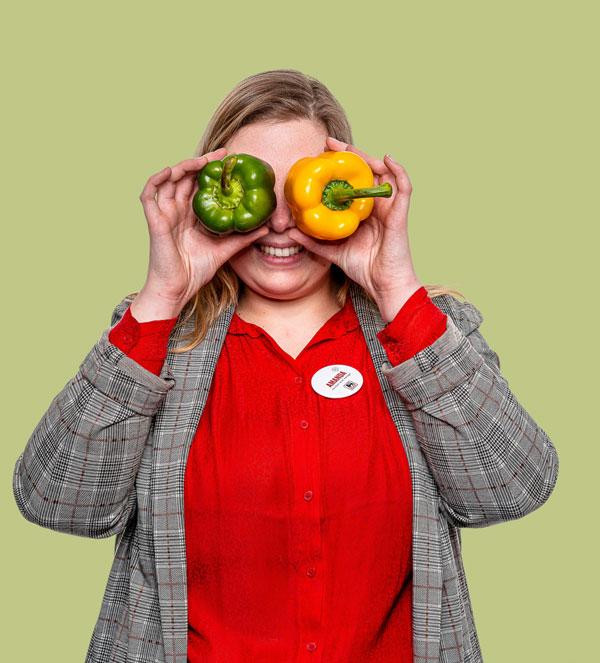 Vrouw rood hemd houdt twee paprika's voor ogen